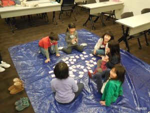children playing a card game on the floor